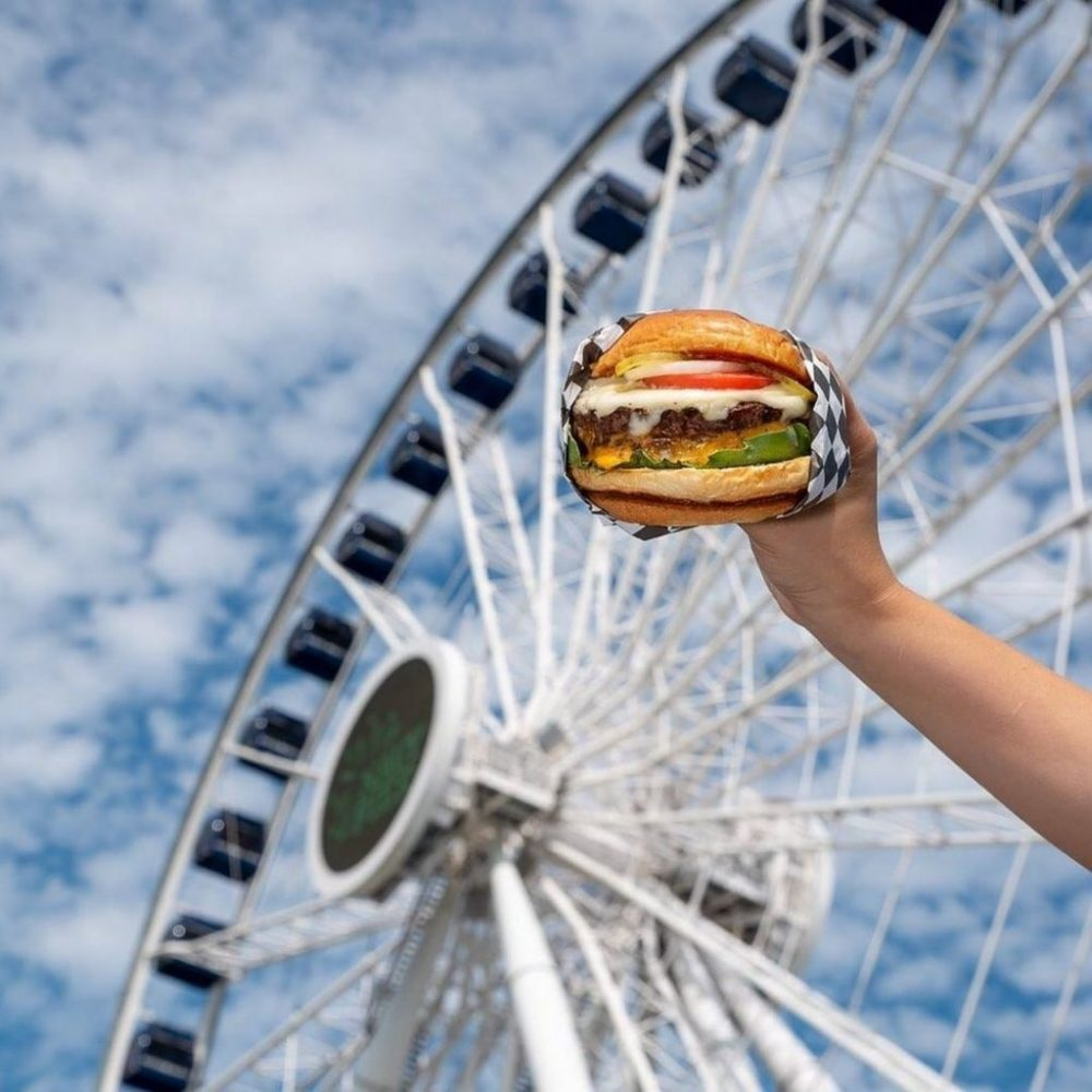 hand holding a burger in front of chicago navy pier