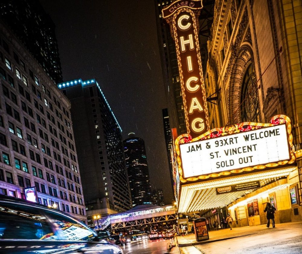 People walking by Chicago Theater building at night