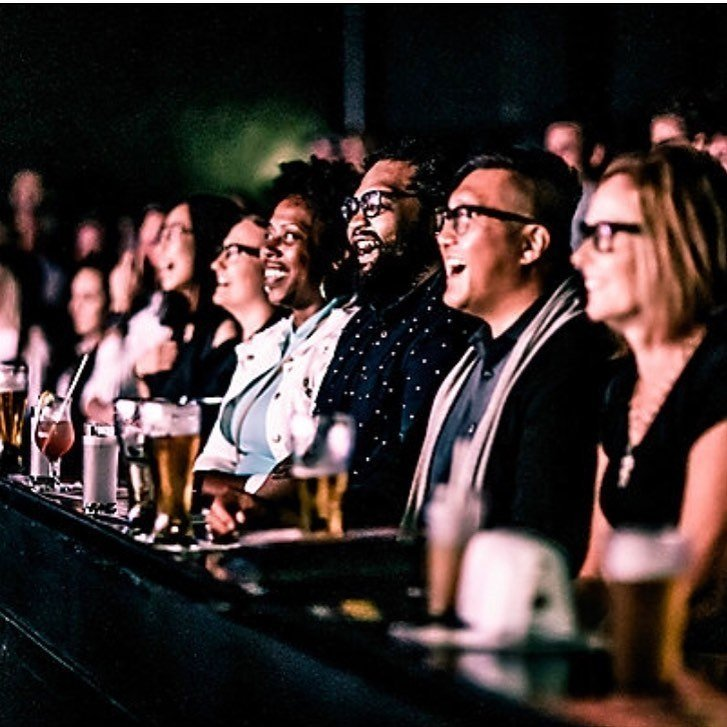 People laughing and enjoying a show at The Second City while having drinks