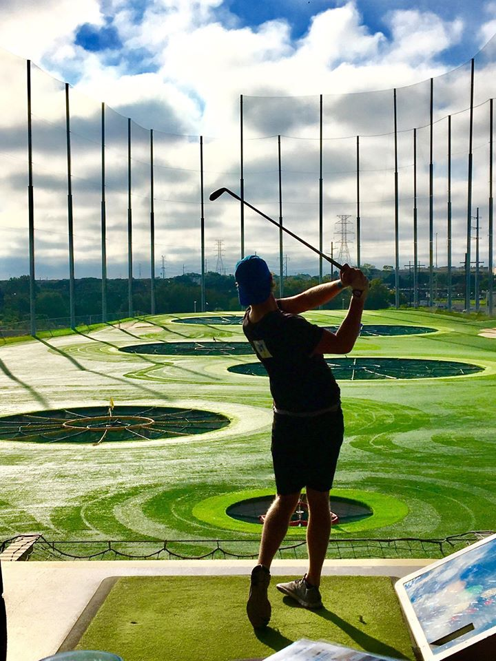 A man playing at Topgolf | things to do in houston