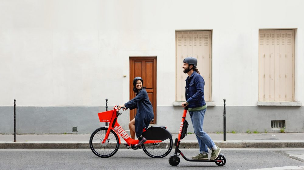 A couple using bike and e-scooter | things to do in denver
