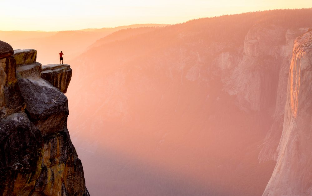 A hiker stands at the edge of a cliff at Taft Point overlooking El Capitan | things to do in yosemite