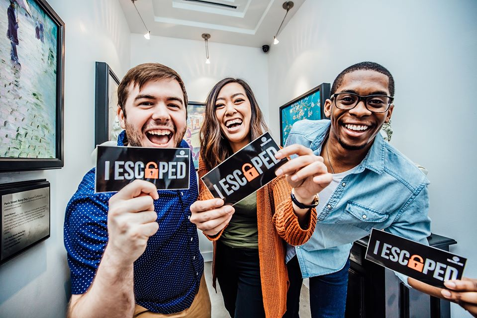 """Friends showing their """"I escaped"""" sticker at The Escape Game Nashville 