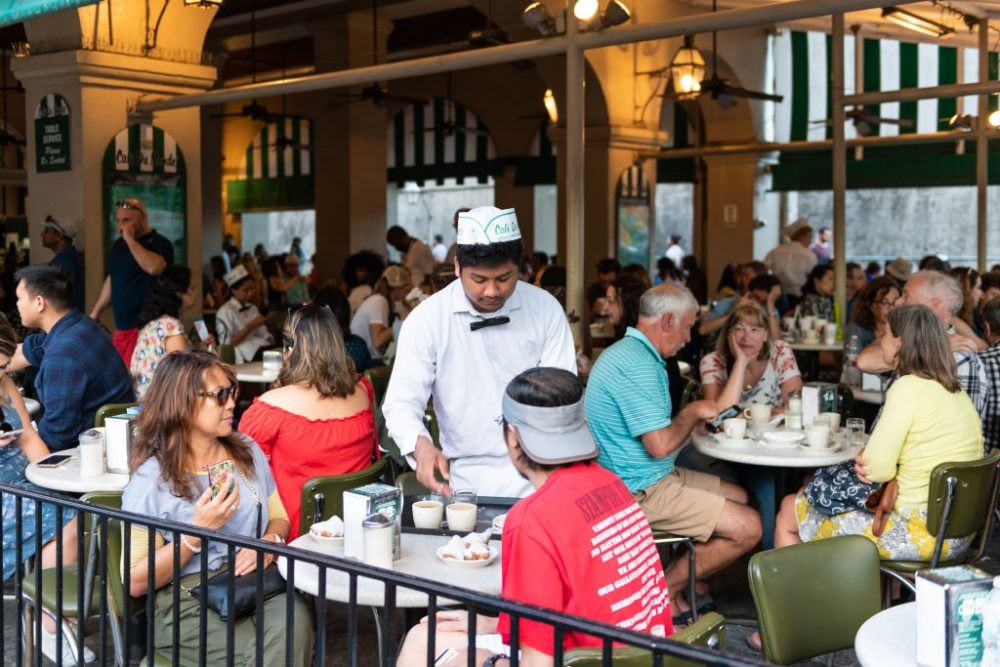 People eating in Cafe Du Monde restaurant | best things to do in new orleans