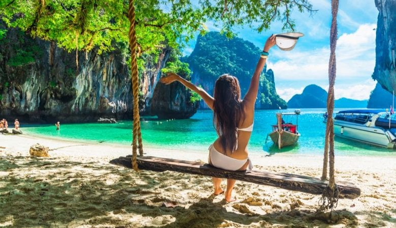 Happy woman in bikini arms open feeling freedom sitting on wooden swing under tree and looking destinations beach