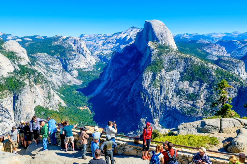 Tourists enjoy a sunny day to visit the Yosemite National Park with Half Dome in the background | things to do in yosemite