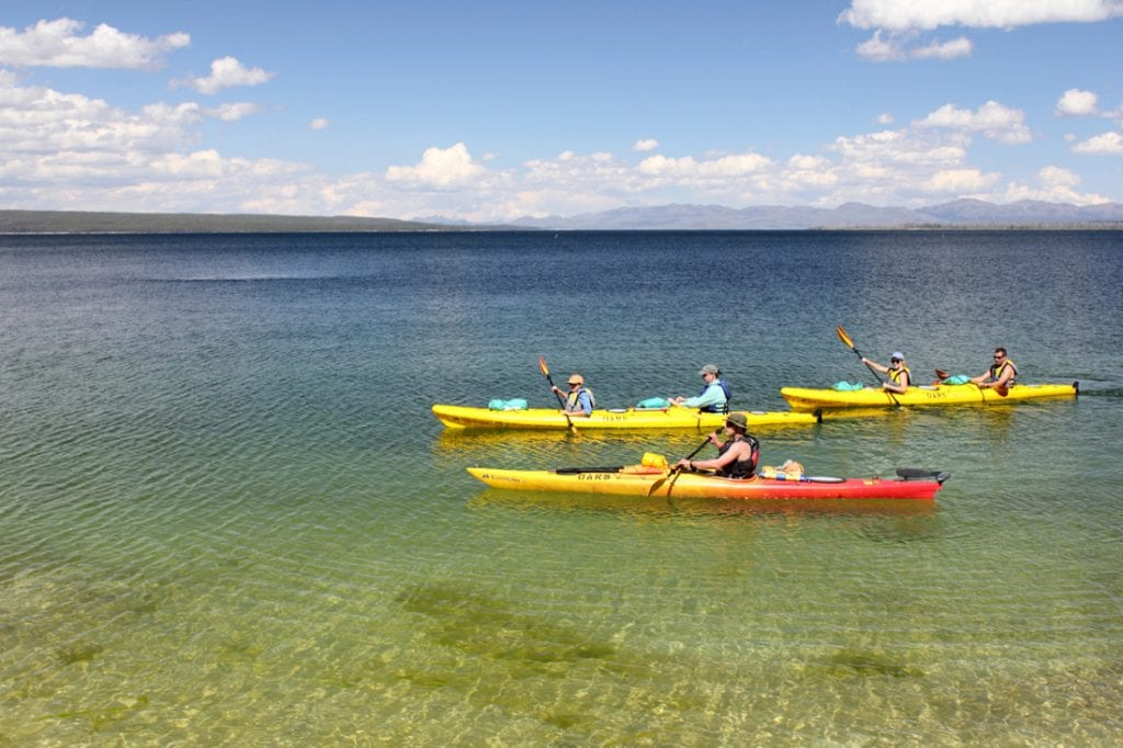 Tourists in kayaks paddle in the West Thumb Geyser Basin, on the shore of Lake Yellowstone | best things to do in yellowstone