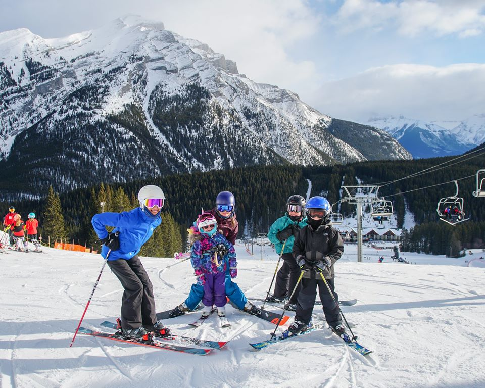 A family enjoying the heat of the sun skiing at Mount Norquay Ski Resort | things to do in banff