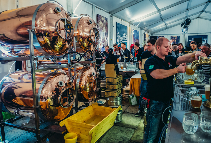 Bartender pours beer during Pilsen Fest in tent located in Pilsner Urquell Brewery area | things to do in prague