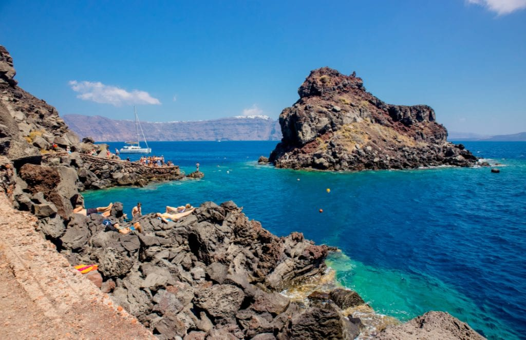 People tourists swimming and sunbathing in a popular cliff jumping spot at Ammoudi Bay | best things to do in santorini