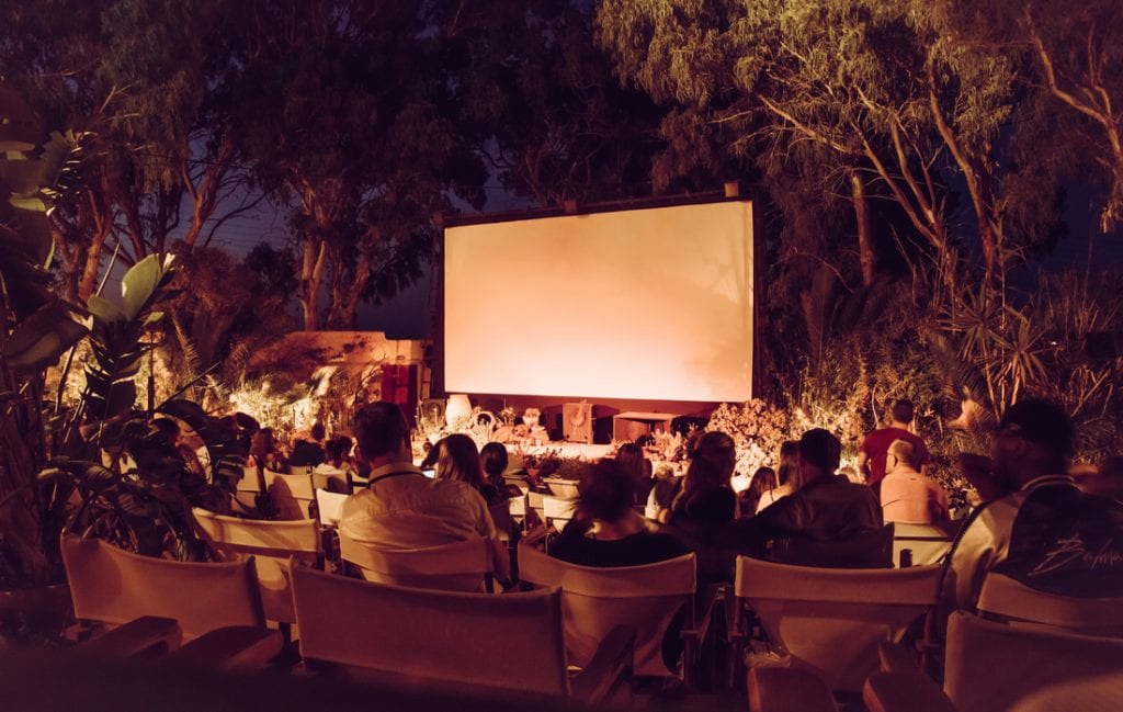 People waiting movie to begin in no roof and open air movie theater, Santorini, Kamari | best things to do in santorini