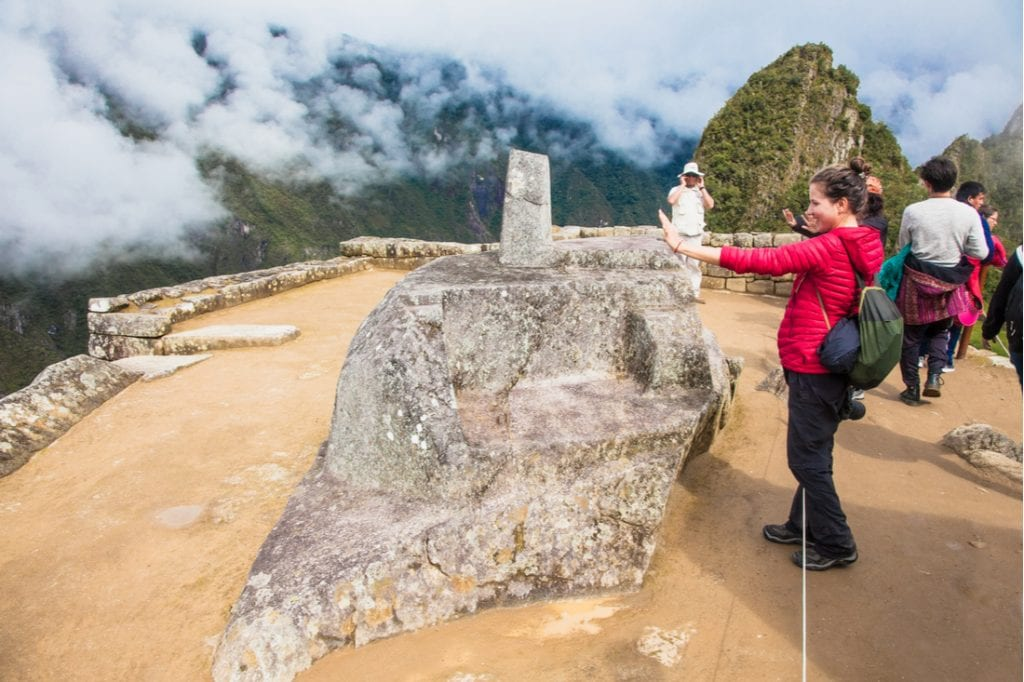 Tourist in front of Intihuatana stone | best things to do in machu picchhu