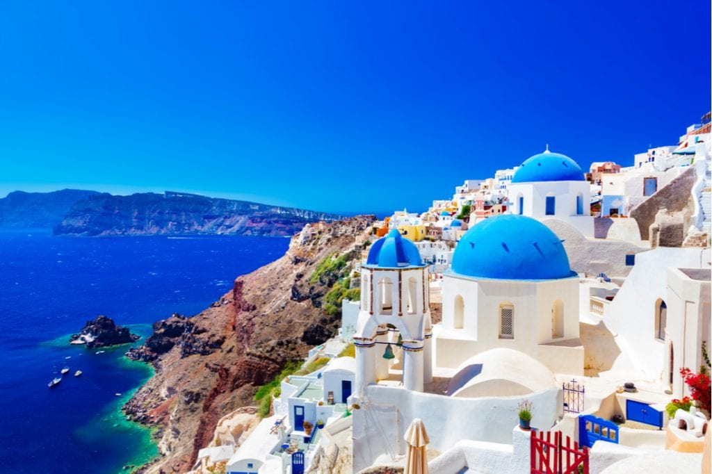 Traditional and famous houses and churches with blue domes over the Caldera, Aegean sea | best things to do in santorini